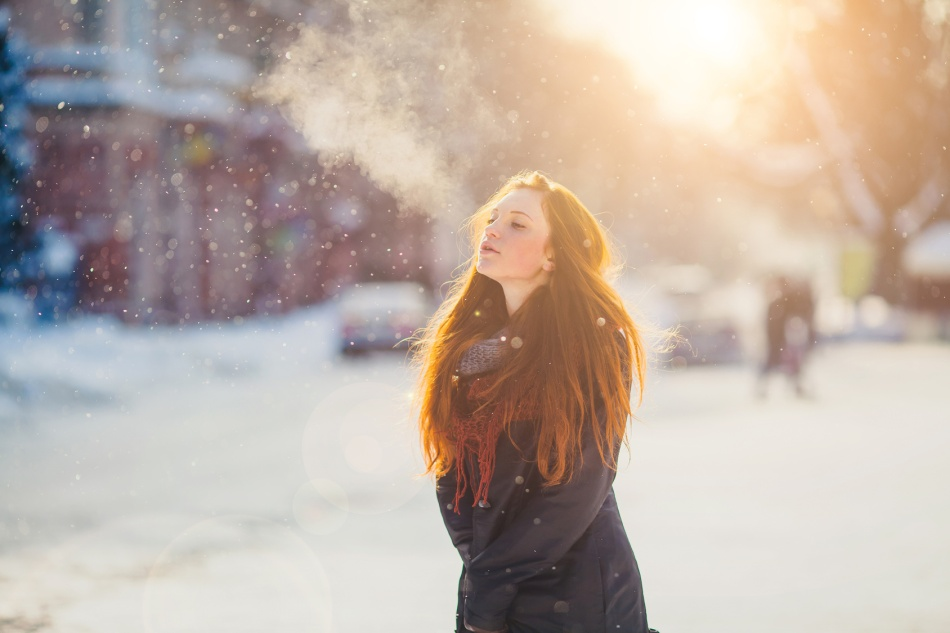 Positive redhead girl on the sun in frozen winter day